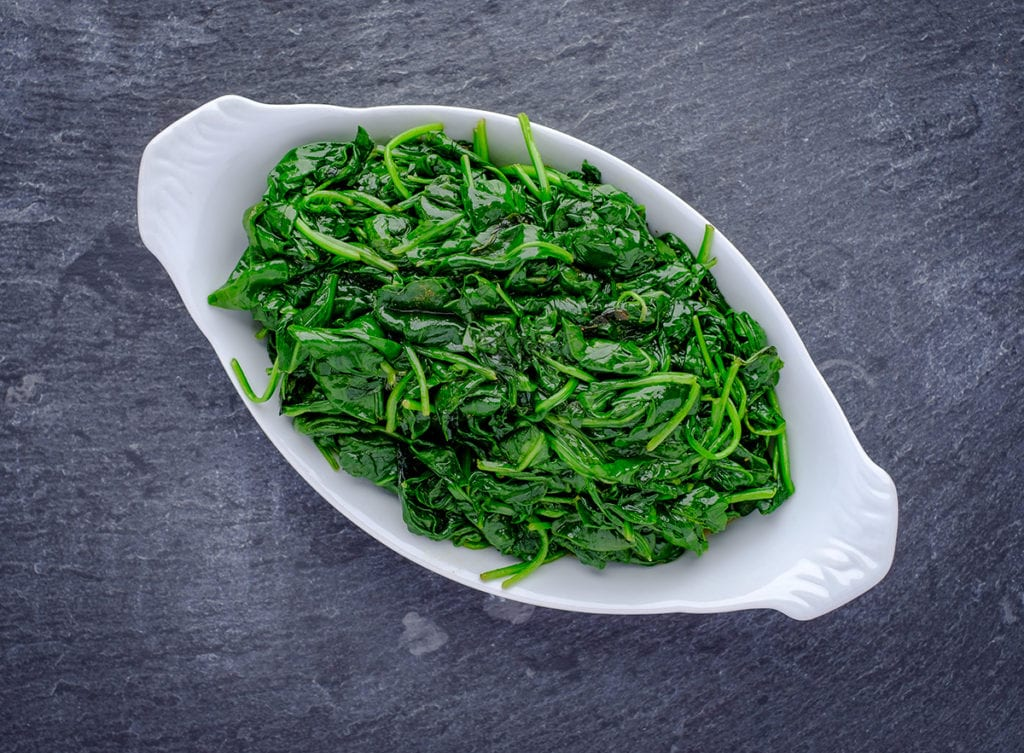 Sautéed Spinach. White dish with sauteed spinach sitting a black slate surface.