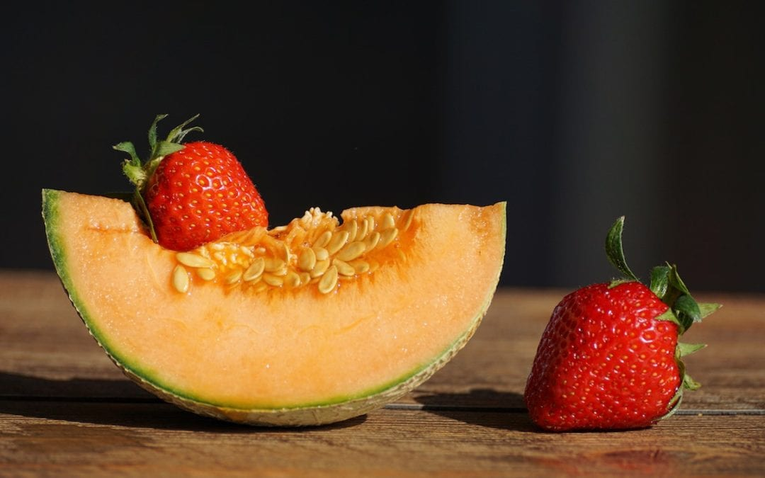 Health Benefits of Cantaloupe | sliced cantaloupe with stawberries at the side on top of a wooden table.